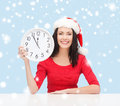 Woman in santa helper hat with clock showing christmas x mas winter happiness concept smiling Stock Image