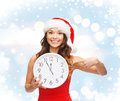 Woman in santa helper hat with clock showing christmas x mas winter happiness concept smiling Royalty Free Stock Image