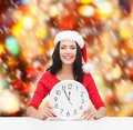 Woman in santa helper hat with clock showing christmas x mas winter happiness concept smiling Stock Photography