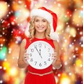 Woman in santa helper hat with clock showing christmas x mas winter happiness concept smiling Stock Photo