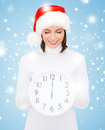 Woman in santa helper hat with clock showing christmas x mas winter happiness concept smiling Royalty Free Stock Photography