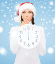 Woman in santa helper hat with clock showing christmas x mas winter happiness concept smiling Stock Images