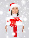 Woman in santa helper hat holding gift box christmas xmas winter and hapiness concept smiling Royalty Free Stock Photo