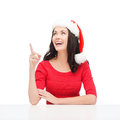 Woman in santa helper hat pointing to something christmas x mas winter happiness concept smiling Stock Image