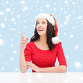 Woman in santa helper hat pointing to something christmas x mas winter happiness concept smiling Royalty Free Stock Photo
