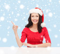 Woman in santa helper hat pointing to something christmas x mas winter happiness concept smiling Royalty Free Stock Image