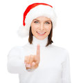 Woman in santa helper hat pressing vitrual button christmas x mas winter happiness concept smiling Stock Photography