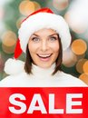Woman in santa helper hat with red sale sign Stock Photos
