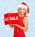 Woman in santa helper hat with red sale sign shopping gifts christmas x mas concept smiling Stock Images