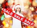 Woman in santa helper hat with red sale sign shopping gifts christmas x mas concept smiling Stock Photography