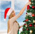 Woman in santa helper hats decorating a tree christmas x mas winter happiness concept smiling hat christmas Royalty Free Stock Photos