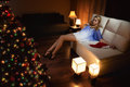 Woman with santa s hats remain all alone young sitting on sofa Stock Image