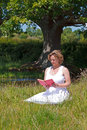 Woman sat in a meadow reading a book white dress besides stream on bright summers day Royalty Free Stock Images