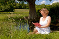 Woman sat by a stream reading in white dress book on bright summers day Stock Photography