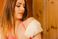 Woman in sauna with exfoliating glove skincare young wood finnish spa massaging skin girl bikini relaxing concept Stock Photography