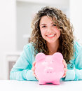 Woman saving money happy in a piggybank and smiling Stock Photos