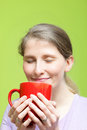 Woman savouring mug hot coffee smiling bliss as breathes rich aroma Royalty Free Stock Image