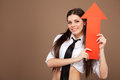 Woman in a schoolgirl costume holding an arrow sign Stock Photo