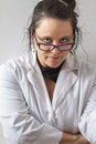 Woman scientist wearing a white lab coat against a white wall Royalty Free Stock Images