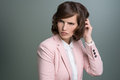 Woman scratching her head with a puzzled frown attractive young brunette businesswoman in stylish pink jacket perplexed over grey Royalty Free Stock Photography
