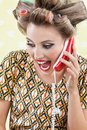 Woman screaming while holding retro phone young with hair curlers out a telephone Royalty Free Stock Photo