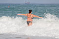 Woman at the sea in swimwear overweight young in swimsuit comes in water in time of surf rear view Royalty Free Stock Photography