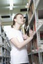 Woman searching books in library young women through the several bookshelves Royalty Free Stock Images