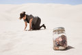 Woman searching for jar of coins in desert Royalty Free Stock Photo
