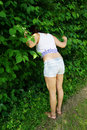 Woman searching for something in the bushes young sticking her head into as if Royalty Free Stock Images