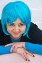Woman seeing herself in blue wig young smiling to as she tries on a on a bright background Royalty Free Stock Photos