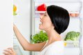 Woman seeks food in the opened fridge full of vegetables and fruit concept of healthy and dieting Royalty Free Stock Photo