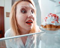 Woman sees the sweet cake in  fridge Royalty Free Stock Photo