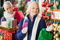 Woman selecting christmas ornaments at store senior women with men holding presents in background Stock Image