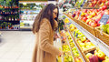 Woman selecting fresh red apples in grocery store produce department and putting it in plastic bag. Young pretty girl is Royalty Free Stock Photo