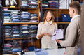 Woman seller assisting man in choosing shirt in men's cloths s Royalty Free Stock Photo