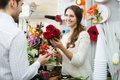 Woman seller offering flowers man smiling women male client Stock Image