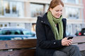 Woman sending or receiving a text message young in autumn clothes reads writes on smartphone photographed on city street with cars Royalty Free Stock Photos