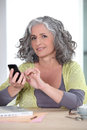 Woman sending text message grey haired Royalty Free Stock Photos