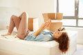 Woman sending text message having moved into new home lying on bed relaxing Royalty Free Stock Photo