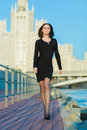 Woman with a serious expression on face walking on waterfront young in black dress Stock Images