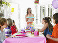 Woman serving cake to children at birthday party happy women the outdoor Stock Photos