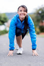 Woman set for running fit in a position to start outdoors Royalty Free Stock Images