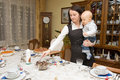 Woman setting table with her child Royalty Free Stock Photo