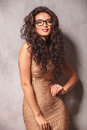 Woman in sexy dress wearing glasses poses at the camera Royalty Free Stock Photo