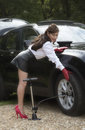Woman with sexy legs pumping up car tyre Royalty Free Stock Photo