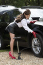 Woman with sexy legs pumping up car tyre