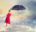 Woman shielding the city from the rain with umbrella young in red dress weather Royalty Free Stock Photos