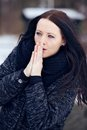Woman shivering in the frozen outdoors rubbing hands together to keep her warm Royalty Free Stock Photography