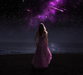 Woman and shooting stars standing in dress at night watching Royalty Free Stock Photography
