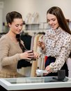 Woman and shop assistant choosing jewellery young women with help Stock Photography